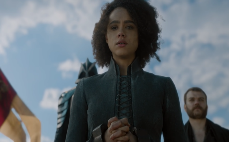 A screenshot of Game of Thrones, Season 8 (2019) that depicts Missandei before her execution. She is looking down towards the camera, which is angled up to show her and the sky. Her hands are bound in chains.